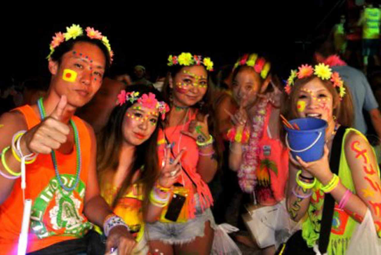 Pessoas de roupas coloridas e pintadas participando da festa na Tailândia